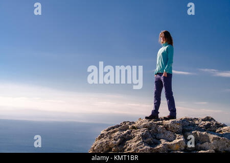 Athletic young woman standing on the rocky top of the mountain against the blue of sky and sea. Face to the camera - Stock Photo