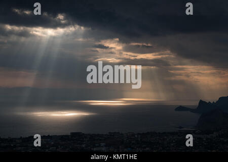 ominous clouds and the bursting rays of light over the gulf sea - Stock Photo