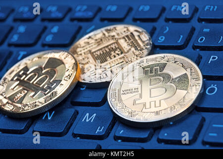 Gold-colored Bitcoin cryptocurrency coin on a computer keyboard - Stock Photo
