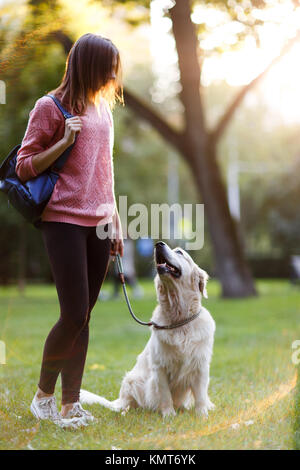 Picture of young woman on walk with retriever in summer park - Stock Photo