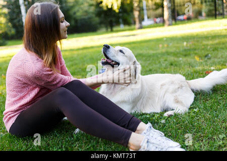 Picture of girl hugging labrador - Stock Photo