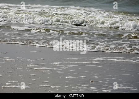 Gentle waves of waters of Baltic Sea can be seen on sandy beach in Kolobrzeg in Poland. It is a view from a beach - Stock Photo