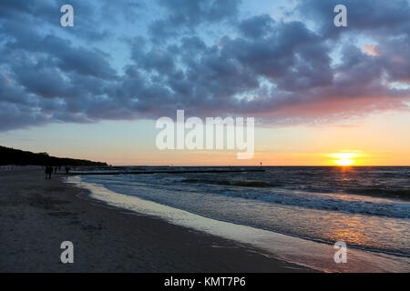 The sunset is seen from the beach of the Baltic Sea in Kolobrzeg. The waves of the sea lightly hits the sandy beach - Stock Photo