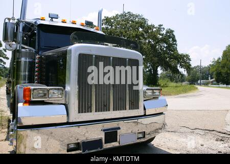 Black huge lorry american truck with stainelss steel in green outdoor - Stock Photo