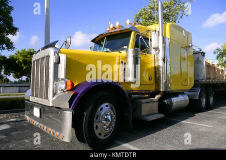 Big yellow american truck in sunny blue sky day - Stock Photo
