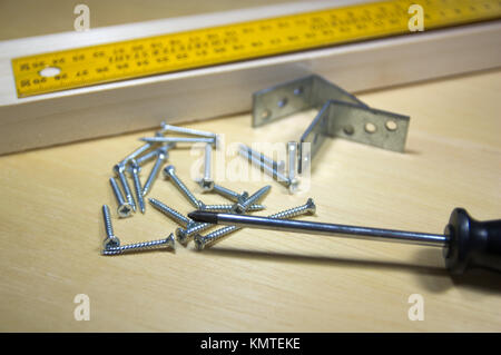 A carpentry tools, a rule on a wooden slat in which they are going to put some screws. - Stock Photo
