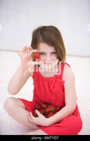 Caucasian girl showing nice strawberries - Stock Photo