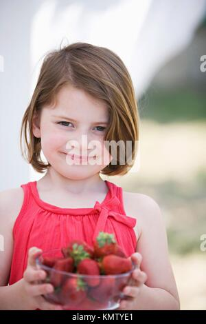 Caucasian girl holding a bowl with nice strawberries - Stock Photo