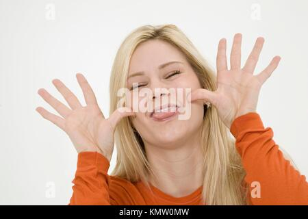 Young woman posing on a white background acting silly - Stock Photo