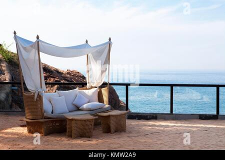 deck chair by the sea in a hotel resort in Kerala state india - Stock Photo