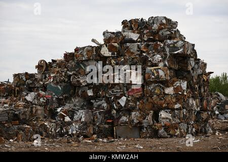 Large pile of stacked compacted crushed compressed scrap metal cubed blocks for scrap metal recycling in the USA. - Stock Photo