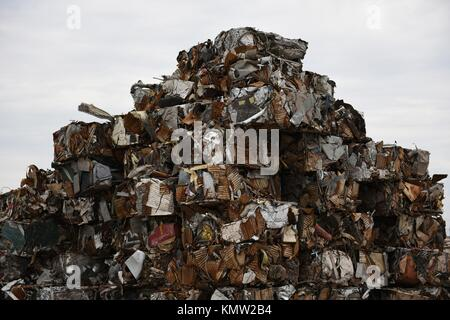 Large tall stack of compacted compressed scrap metal cubes for scrap metal recycling in the USA. - Stock Photo