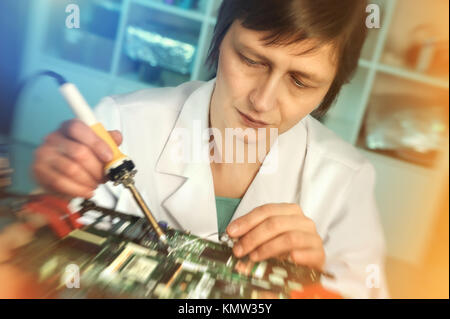 Mature caucasian female engineer or tech repairs electronic device in hardware repair shop. This image is toned. - Stock Photo