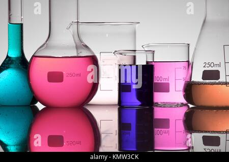 group of beakers with colored liquid on a white background - Stock Photo