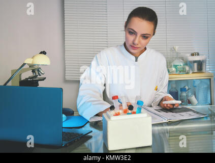 Physician or medtech in white coat working with patients samples. - Stock Photo