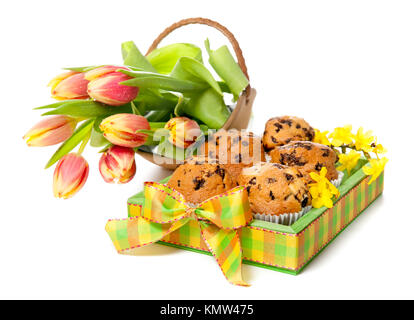 Tray of muffins decorated in spring colors and a bunch of tulips - Stock Photo