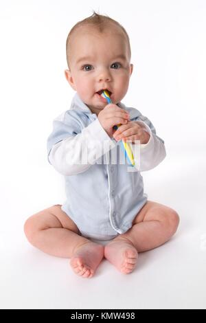 Baby boy is pretending to brush his teeth - Stock Photo