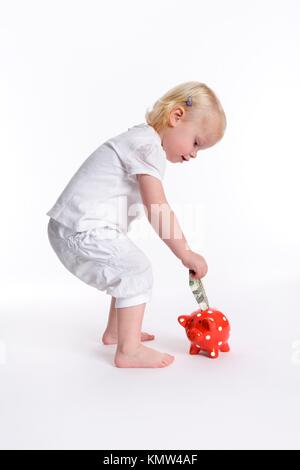 Toddler girl is putting a dollar in a piggy bank - Stock Photo