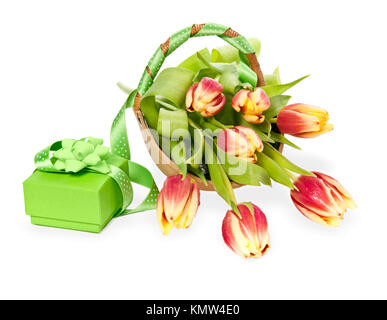 Gift box with bow and ribbon next to a bunch of red-yellow tulips on white background; focus on the box - Stock Photo