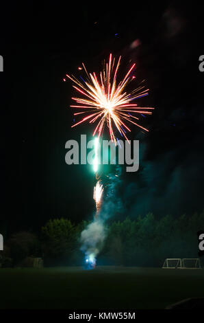 Fireworks launching into the sky and exploding at a public display. - Stock Photo