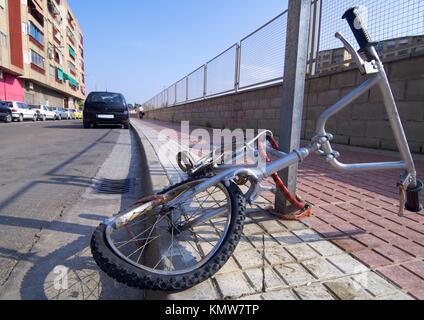 broken bike abandoned in a street - Stock Photo