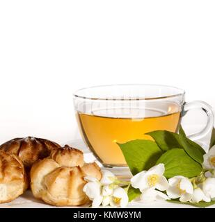 cup of herbal jasmine tea with éclair - Stock Photo