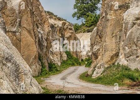 Winding road in green landscape under blue skies - Stock Photo