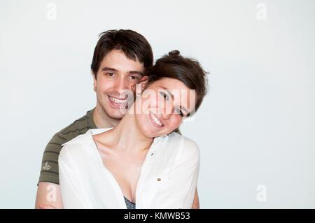Young couple smiling and looking at the camera - Stock Photo