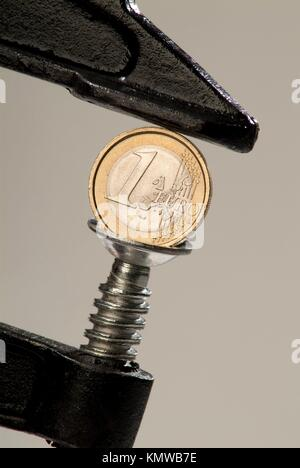 A one euro coin in a tight grip - Stock Photo