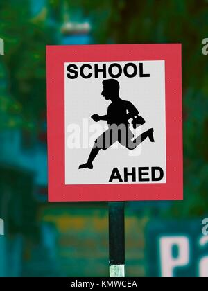 Road signboard indicating school ahead - Stock Photo