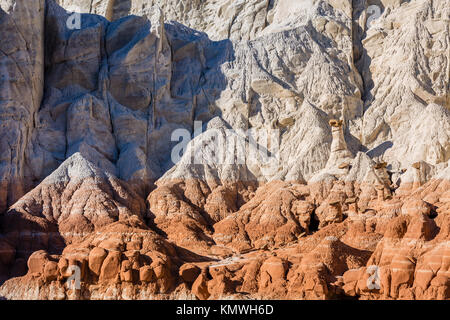 Toadstool Hoodoos hiding amongst the white and chocolate cliff layers of the Grand Staircase in Grand Staircase - Stock Photo