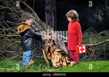 A boy and a girl heal a fallen tree, Un niño y una niña curan un arbol caido - Stock Photo