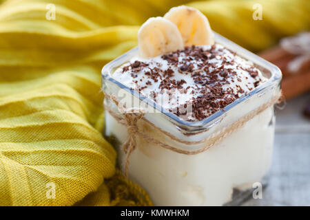 Creamy pudding with banana, chocolate and cinnamon for breakfast. - Stock Photo