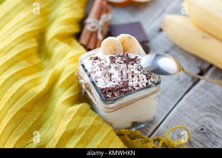Creamy pudding with banana, chocolate and cinnamon for breakfast. - Stock Photo
