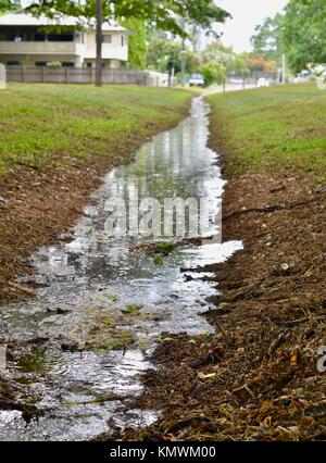 Water running in a drain in a forested park after a tropical downpour, Townsville, Queensland, Australia - Stock Photo