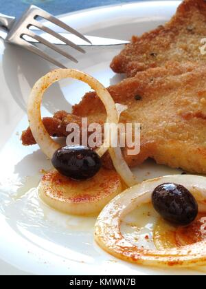 Breaded steak with onions and olives - Stock Photo
