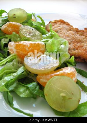 Grape and tangerine salad with breaded steak - Stock Photo
