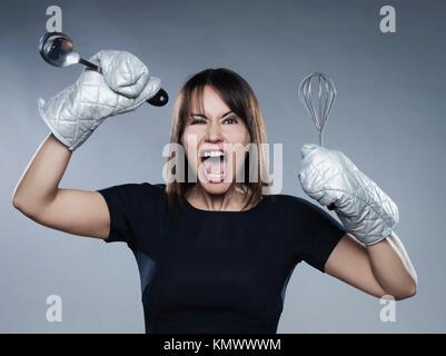 caucasian woman strain holding kitchen utensils isolated studio on grey background - Stock Photo