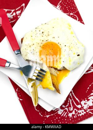 A freshly fried egg on a piece of toast - Stock Photo
