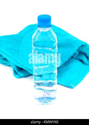 A bottle of water and a sports towel isolated against a white background - Stock Photo