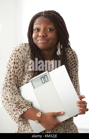 Teenage girl with a funny expression carrying a scale on white background - Stock Photo