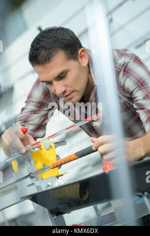 factory man worker checking metal plank straightness at workshop - Stock Photo