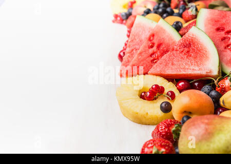 Various summer fruits and berries on white table background. Healthy food and vegetarian eating concept - Stock Photo