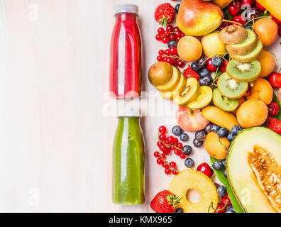 Red and green smoothies and juices beverages in bottles with various fresh organic fruits and berries ingredients - Stock Photo