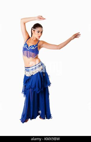 Beautiful Arabic belly dancer harem woman in blue with silver dress and head jewelry with gem dancing swirling her - Stock Photo