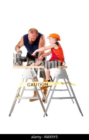 Cute son is helping dad cutting a wooden plank with a heavy duty circle saw as he is pointing out how to do it, - Stock Photo
