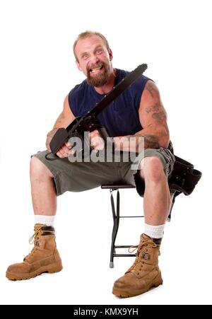 Crazy Caucasian man with tattoos and chainsaw sitting on stool with strong facial expression, isolated - Stock Photo