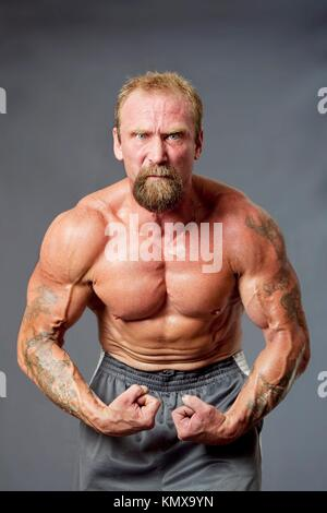 Middle aged Caucasian body builder man flexing muscles showing torso pecs, biceps and veins, isolated - Stock Photo