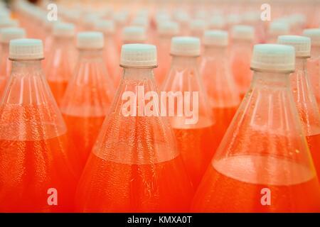 orange juice beverage plastic bottle in factory line - Stock Photo
