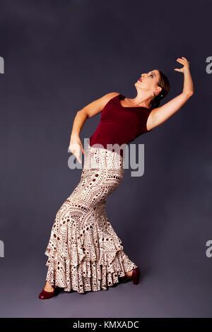 Beautiful female Flamenco dancer doing a typical line pose, wearing modern attire  Spanish woman dancing Flamenco - Stock Photo